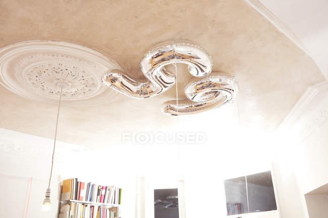 Серебряный номер 65 шаров висит над потолком — стоковое фото