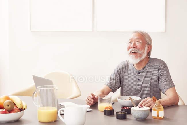 Senior man sitting at breakfast table — Stock Photo
