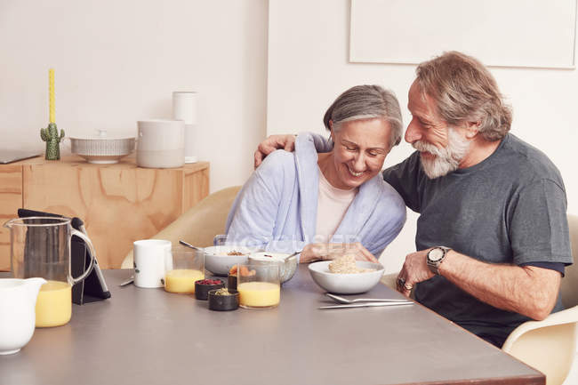 Senior couple laughing at breakfast table — Stock Photo