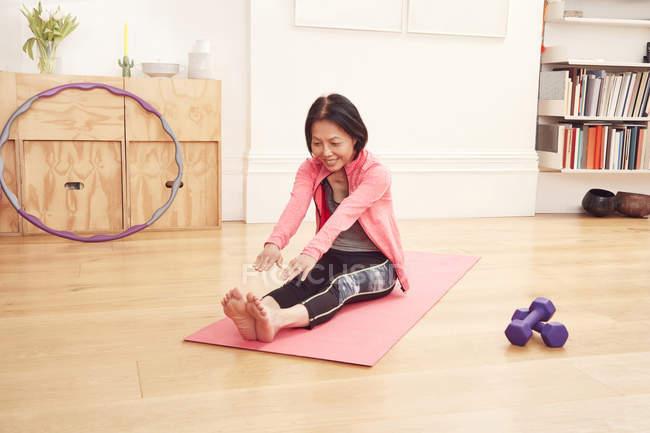 Женщина растягивается на коврике для йоги — стоковое фото