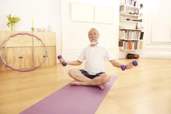 Человек осуществляет с гантелями на гимнастический мат — стоковое фото
