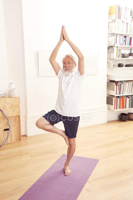 Mann tut Yoga am Gymnastikmatte — Stockfoto