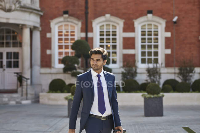 Businessman with wheeled bag on hotel area — Stock Photo