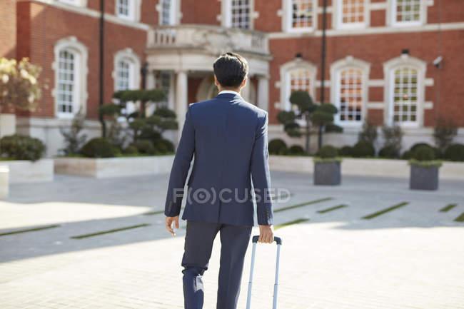 Geschäftsmann läuft mit Rollkoffer — Stockfoto