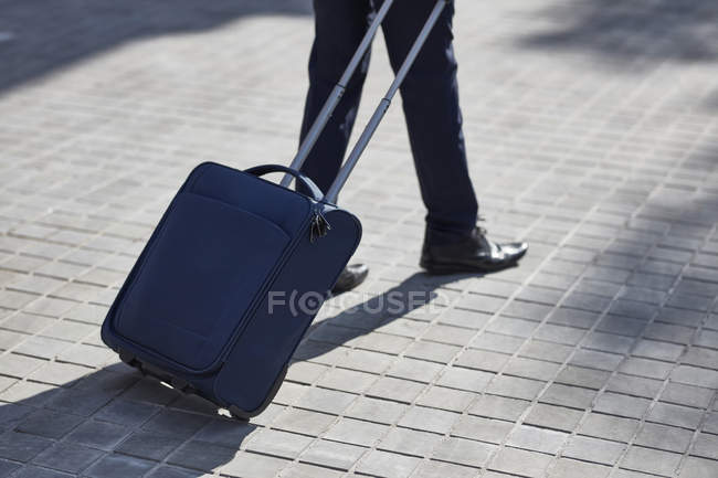 Male legs walking with wheeled luggage bag — Stock Photo