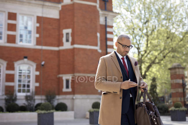 Businessman text messaging on smartphone — Stock Photo