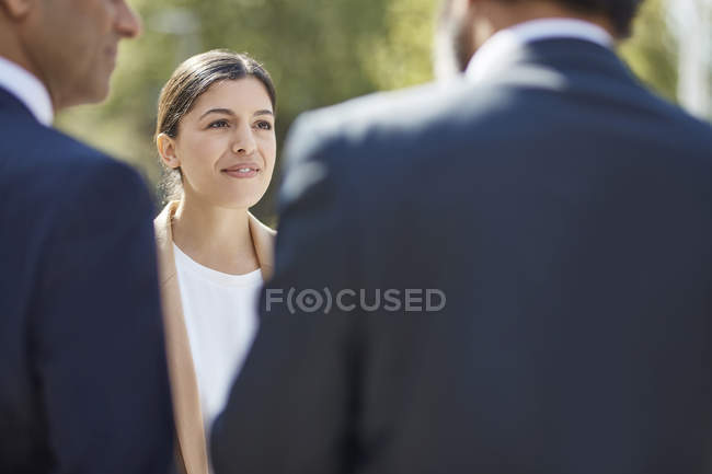 Businesswoman listening to her colleagues — Stock Photo
