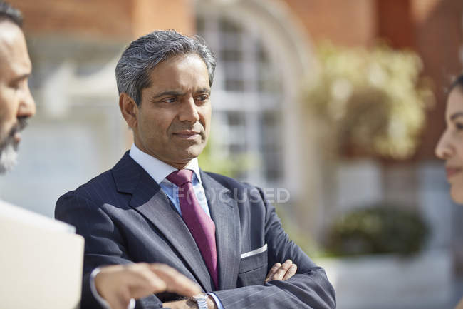 Businesspeople listening to colleague — Stock Photo