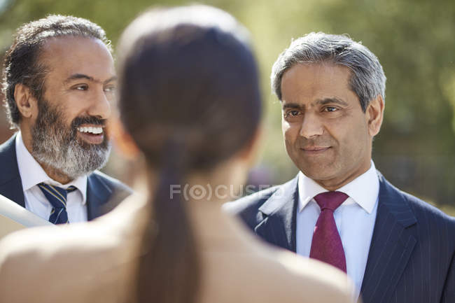 Business colleagues talking with female partner — Stock Photo