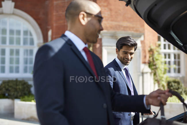 Businessmen unloading luggage from car — Stock Photo