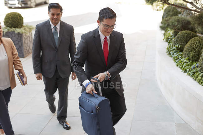 Conceirge carrying luggage for businessman — Stock Photo
