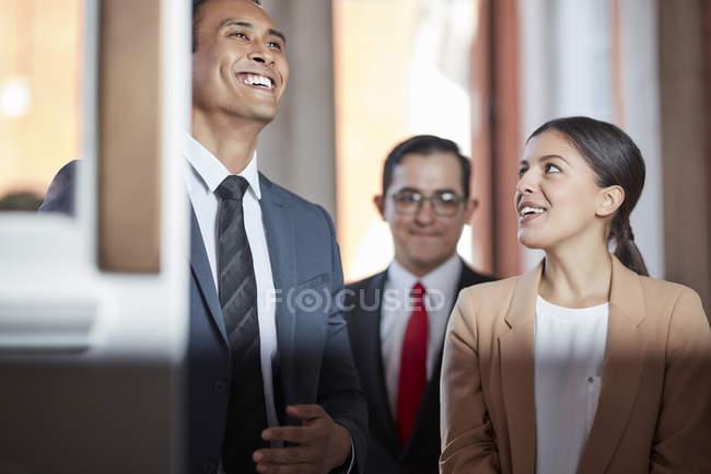Улыбаясь бизнесменов, стоя в дверях — стоковое фото