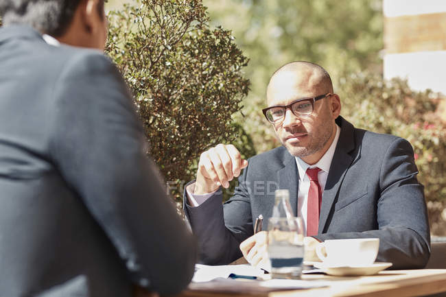 Businessman sitting at cafe with colleague — Stock Photo