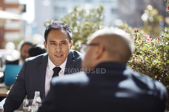 Businessman in meeting with coworker at cafe — Stock Photo