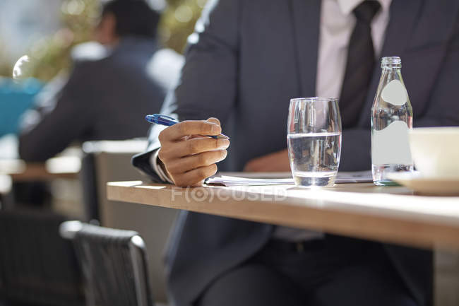Hand of businessman making notes — Stock Photo