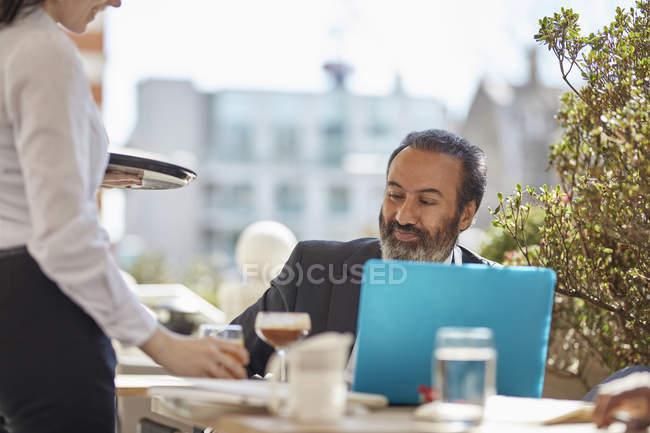 Бизнесмен с ноутбуком в кафе — стоковое фото
