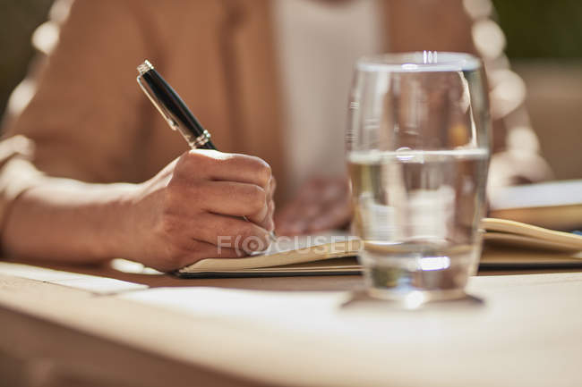 Hand of businesswoman writing notes — Stock Photo