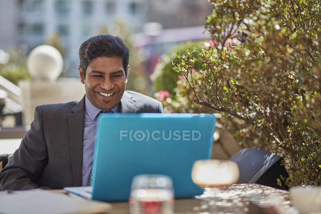 Businessman with laptop at cafe — Stock Photo