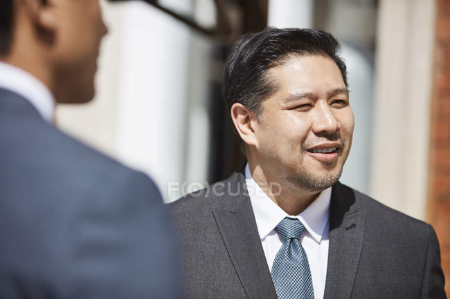 Businessman listening to colleagues outdoors — Stock Photo