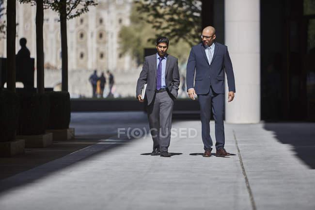 Hommes d'affaires marchant le long du trottoir ensemble — Photo de stock