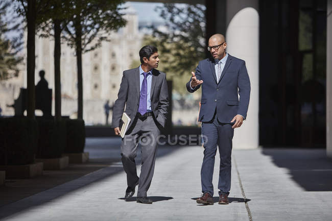 Businessmen walking along sidewalk together — Stock Photo