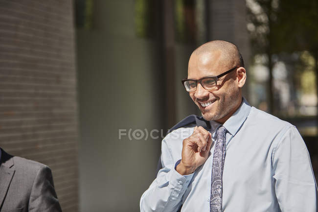 Businessman wearing glasses and walking on street — Stock Photo