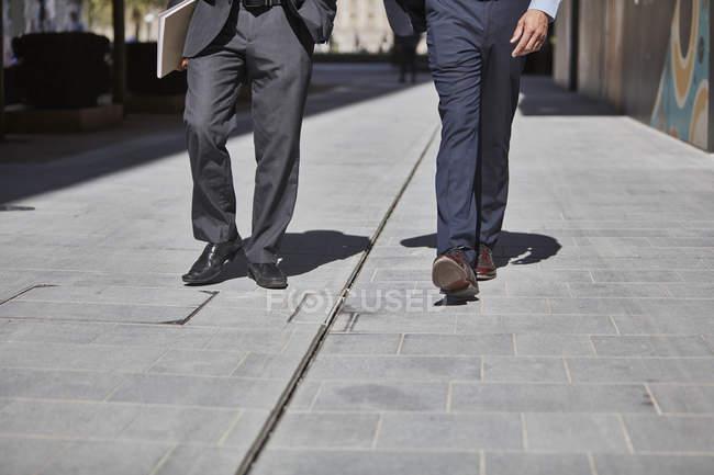 Legs of businessmen walking on sidewalk — Stock Photo