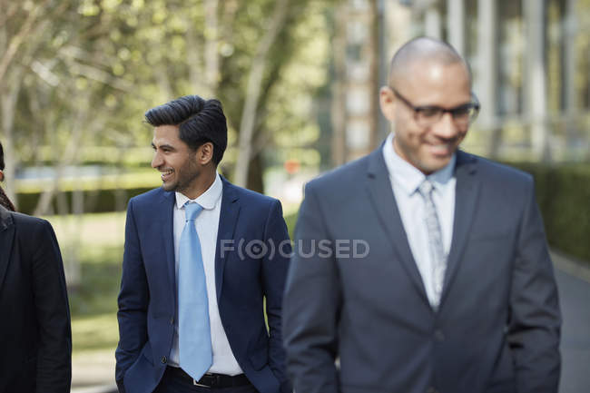 Smiling businessmen walking together — Stock Photo