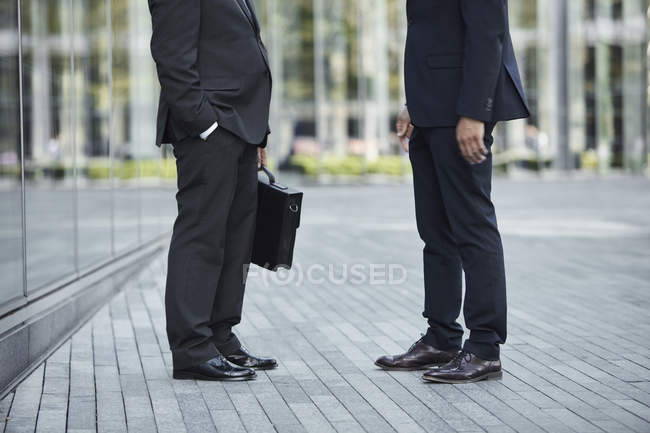 Legs of businessmen talking at park — Stock Photo