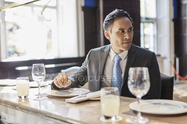 Businessman sitting at bar of restaurant — Stock Photo