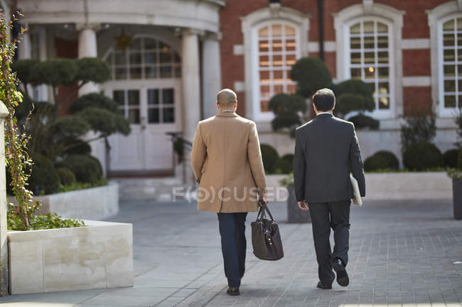 Businessmen walking togehter to hotel entrance — Stock Photo