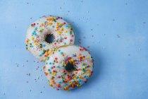 Deux beignets avec glaçage sur la surface bleue — Photo de stock