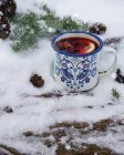 Closeup view of metal mug of hot tea with lemon slice and anise stars on snow — Stock Photo