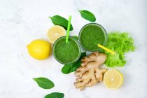 Glasses of spinach with lemon and ginger green smoothie on white surface with ingredients — Stock Photo