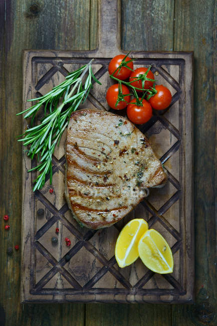 Fish steak with tomatoes, lemons and rosemary — Stock Photo