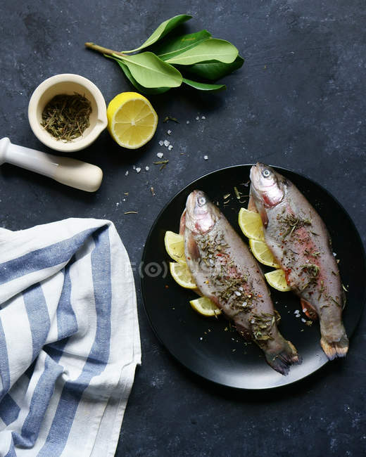 Two trout fish with herbs and lemons — Stock Photo
