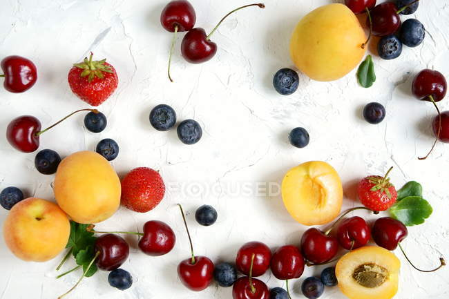 Peaches, blueberries, cherries and strawberries on table — Stock Photo