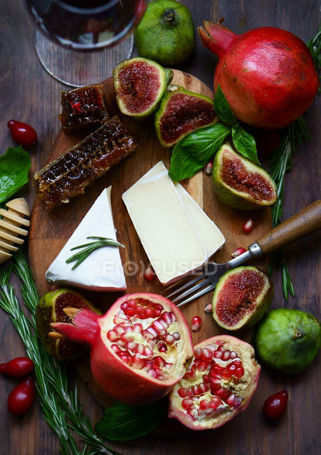Cheese and fruits on board — Stock Photo