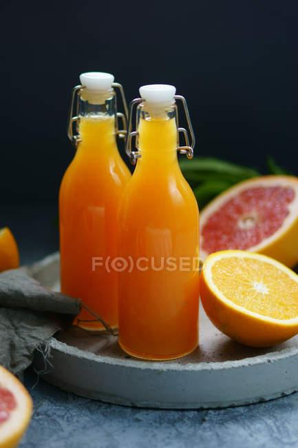 Garrafas com suco e laranjas na bandeja — Fotografia de Stock