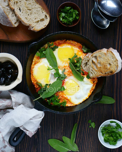 Fried eggs with bread and green leaves — Stock Photo