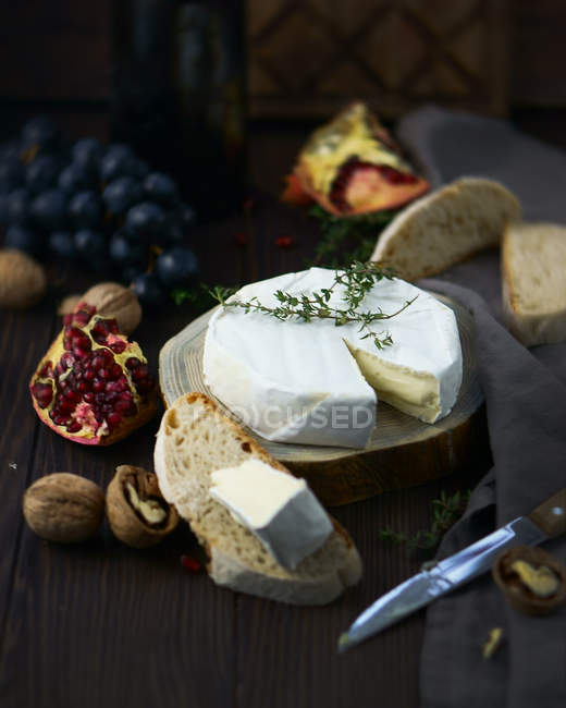 Closeup view of cheese wheel with bread slices, walnuts and pomegranate on wood — Stock Photo