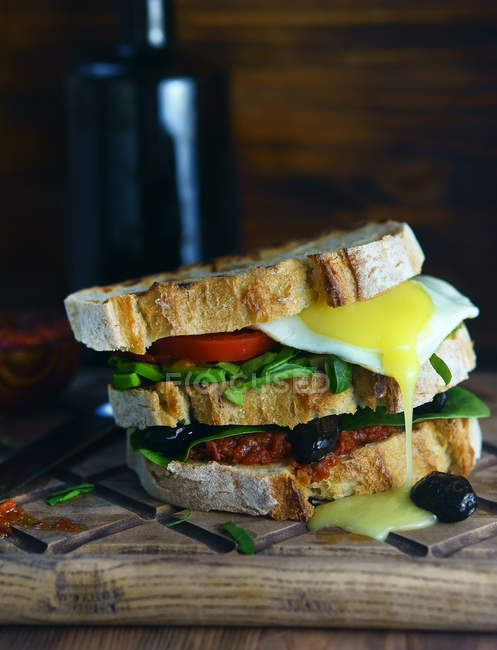 Closeup view of big sandwich with greenery, fried egg, stuffing and olives on wooden board — Stock Photo