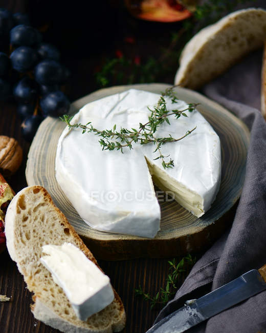 Closeup view of white cheese wheel with bread slices and grapes on wood — Stock Photo