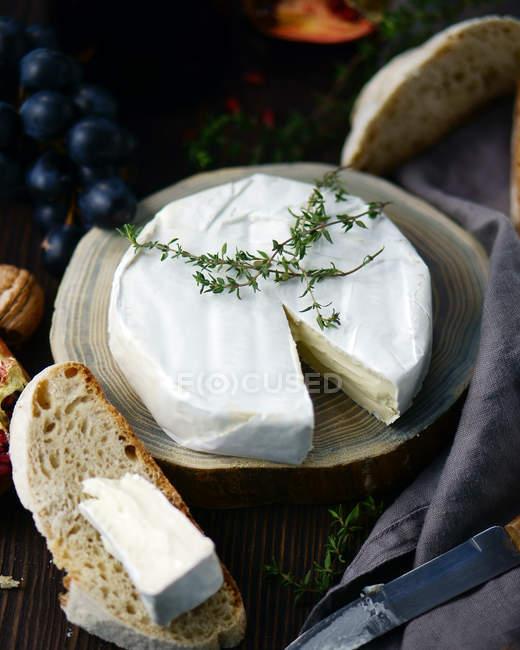 Detailansicht des weißen Käse Rad mit Brotscheiben und Trauben auf Holz — Stockfoto