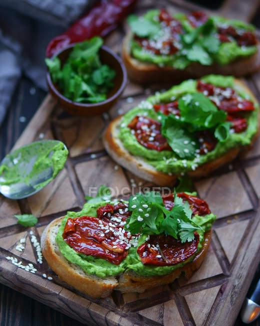 Крупным планом вид бутерброды с зеленым пастой, салями, семена кунжута и Петрушка на деревянной доске — стоковое фото