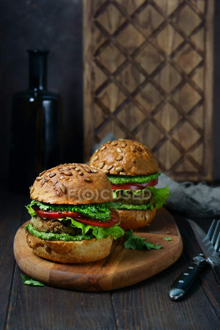 Closeup view of two burgers with sunflower seeds on wooden cutting board — Stock Photo