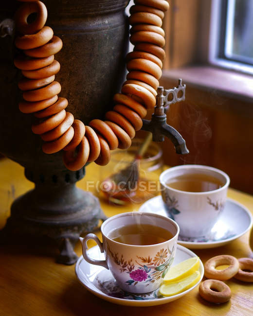 Closeup view of tea cups with samovar, lemon slices and cracknels — Stock Photo