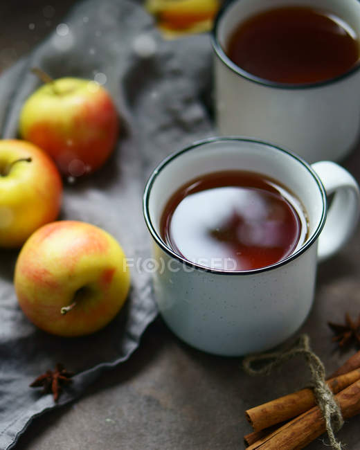 Closeup view of metal cups of tea with apples, cinnamon sticks and anise stars — Stock Photo
