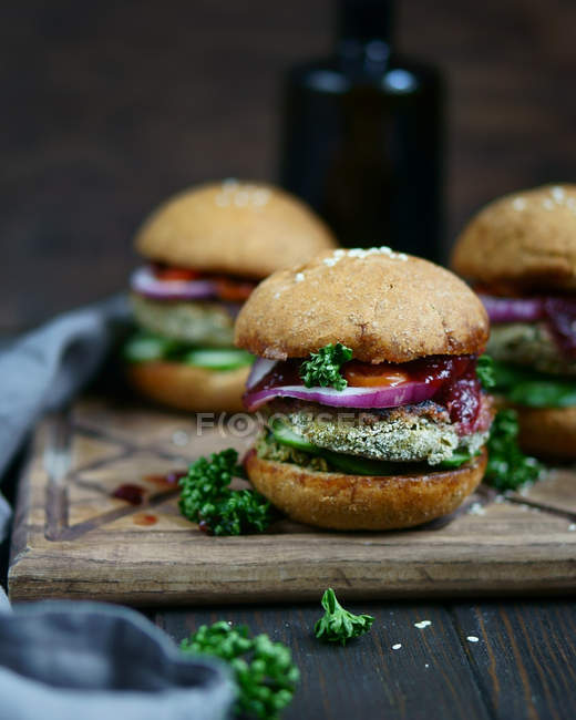 Closeup view of burgers with vegetables and sesame seeds on wooden board — Stock Photo