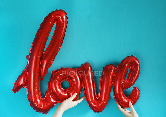 Cropped view of human hands holding air balloon in shape of love word — Stock Photo